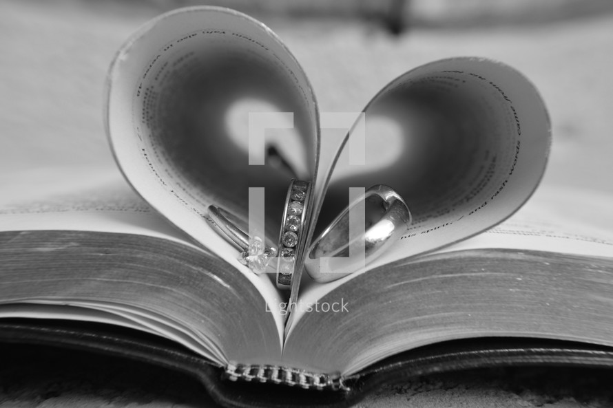 Bible pages folded into the shape of a heart with wedding rings