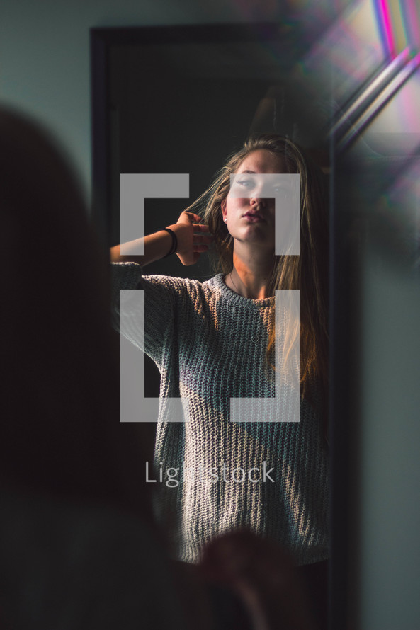 teen girl looking in a mirror
