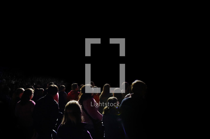 crowd of young people standing in darkness