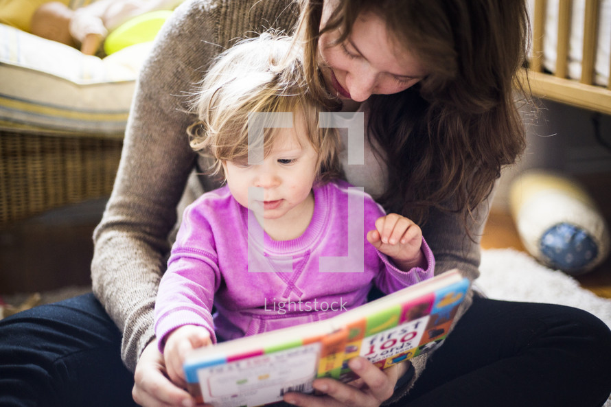 mother and toddler daughter reading together