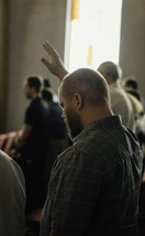 man with a raised hand during a worship service