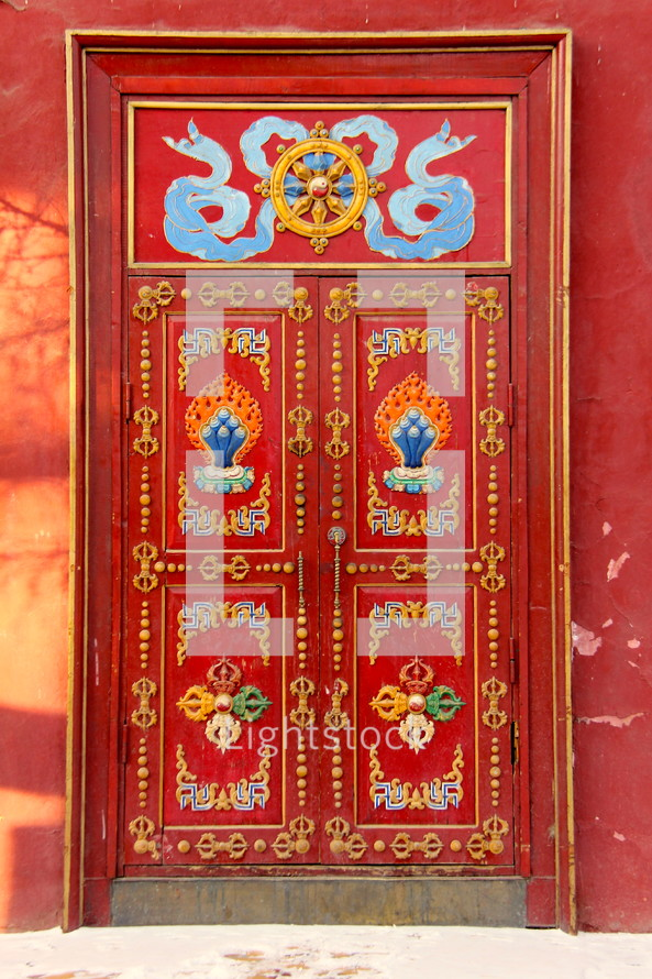 An ornate and detailed red door, entrance to an oriental palace