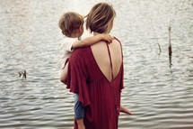 a mother holding her toddler son standing in front of a lake