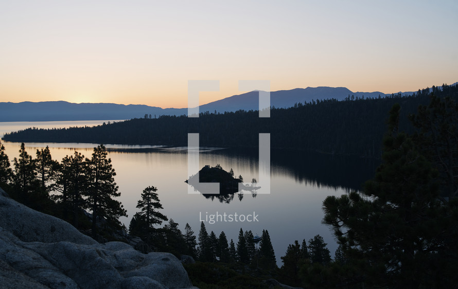 A forest and a lake with mountains in the background before sunrise