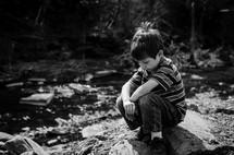 a boy child squatting on a rock