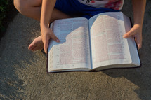 child reading a Bible outdoors