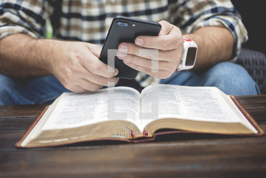 a man texting on his cellphone over the pages of an open Bible