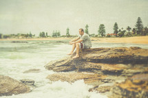 A man sitting on rocks at an ocean shore