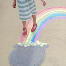 a girl walking towards the pot of gold at the end of a rainbow