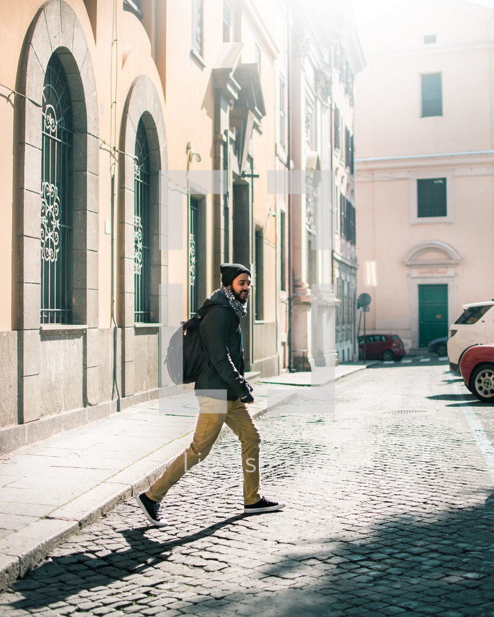 a man with a backpack walking across a cobblestone street