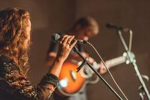 worship leaders singing into microphones