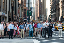 crowd of pedestrians waiting to cross a busy city street