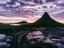 mountain peak under purple clouds at sunset