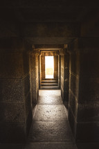 Bright light coming through a doorway at the end of a stone hallway.