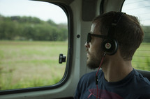 man listening to headphones and looking out a car window