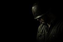 Soldier with head bowed in prayer shot in dramatically soft lighting against a black background.