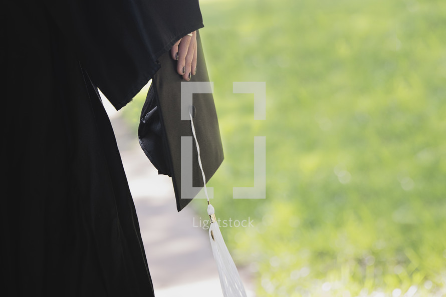 a teen girl holding her graduation cap at her side