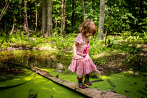 a toddler girl in rain boots exploring a pond