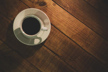 coffee cup and saucer on a wood floor