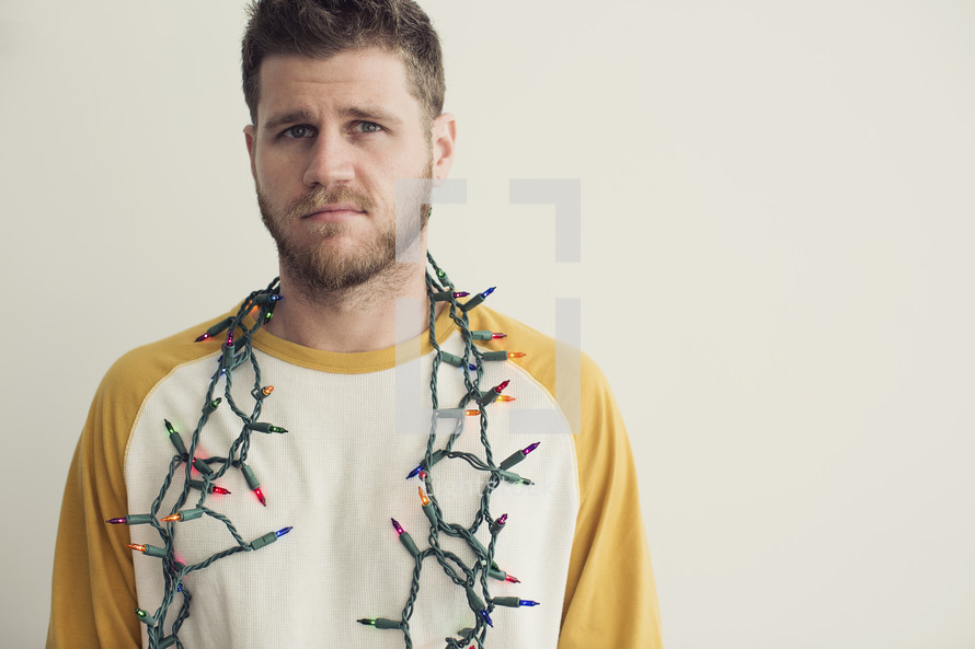 man with a string of Christmas lights around his neck