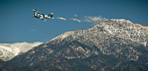 vintage single engine aircraft flying over mountains