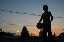 silhouette of a boy child holding a basketball at sunset