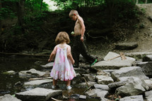 children walking on rocks in a stream