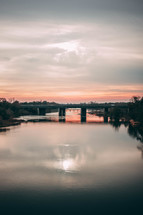 bridge over a river at sunset
