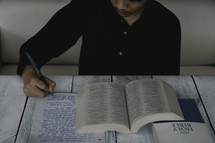 a young man journaling and reading a Bible