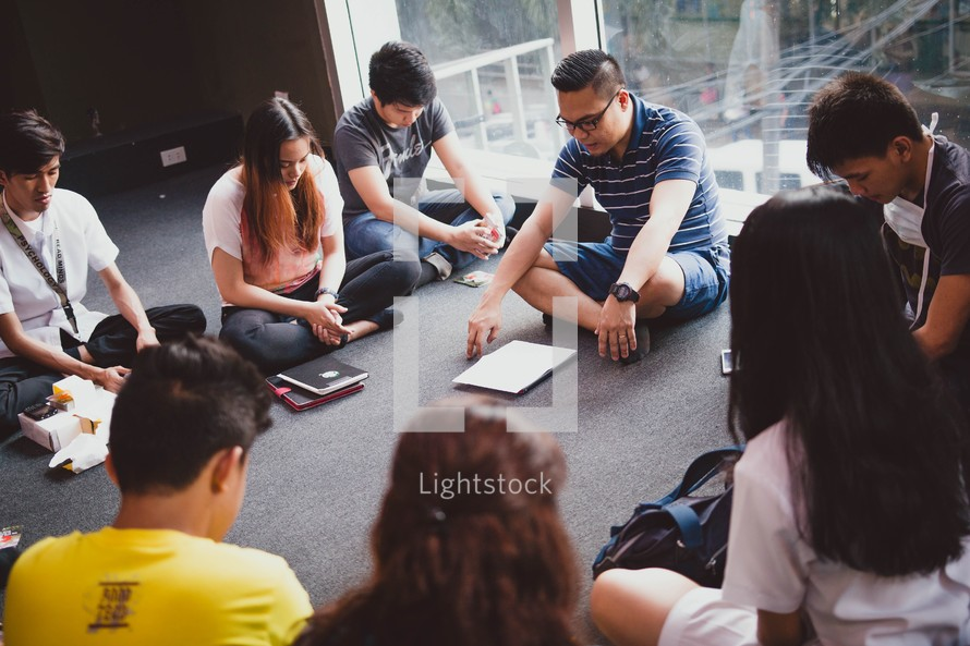young adults praying at a Bible study