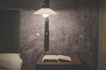 an open Bible on a night stand