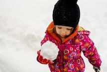 a child building a snowman