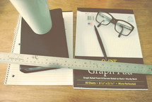 reading glasses and pencil on graph paper