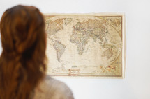 A woman looking at a world map hanging on a wall