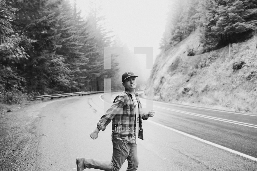 a man in a ball cap dancing on the side of a road