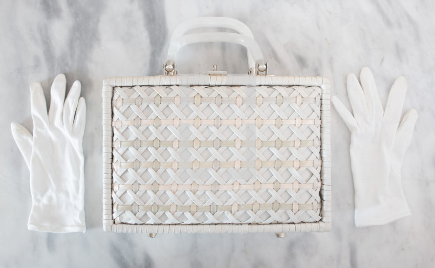White gloves and straw handbag on a marble background