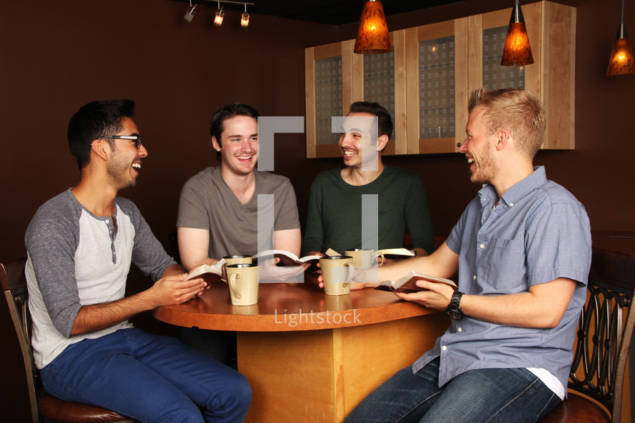 men sitting at a table with Bibles and coffee mugs