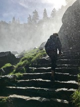 a woman climbing up rocky stairs