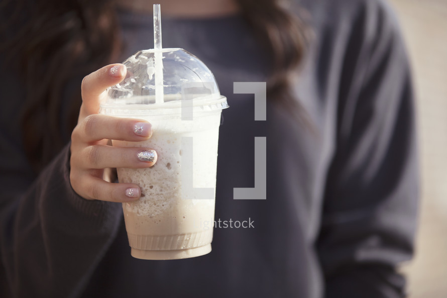 Hand holding a frozen latte.