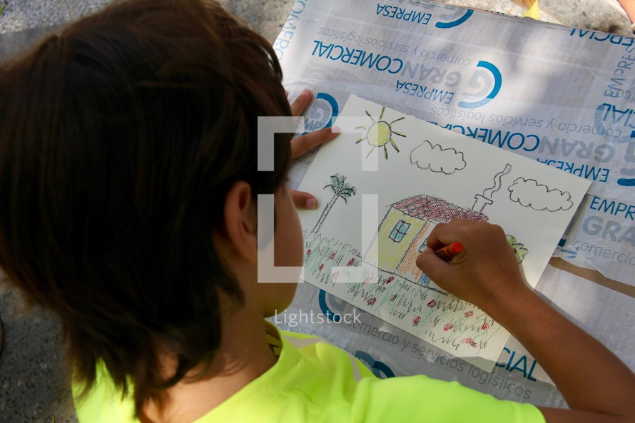 a child coloring a house drawing