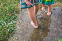 kids playing in a puddle in their barefeet