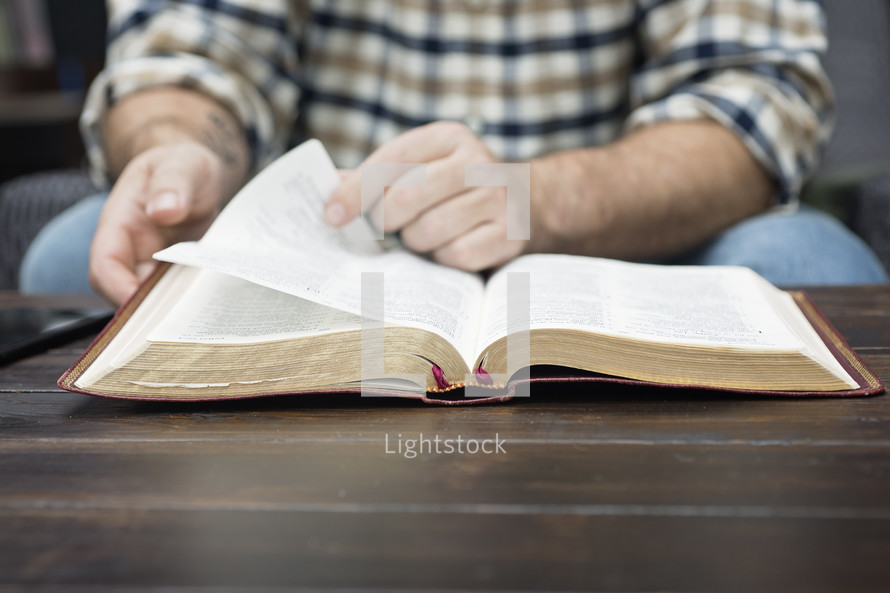 a man reading a Bible on a coffee table