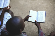 men reading Bibles on a mission trip