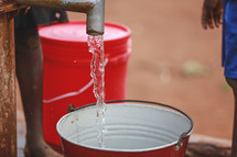 water from a spigot falling into a bucket