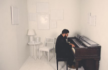a man playing a piano in a white room