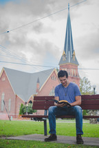 man sitting on a bench reading a Bible and a church in the background
