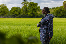 a woman with a camera standing in a field