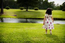 toddler girl in a sundress standing in grass
