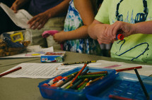 children coloring and using glue sticks
