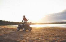 Boy riding four wheeler on beach